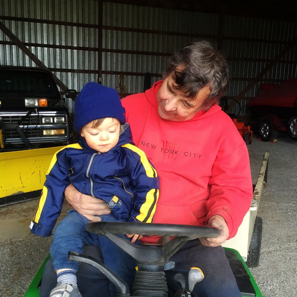 Boo sitting on the John Deere with Gramps